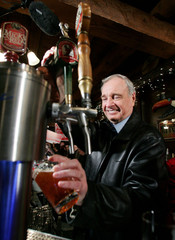 Canadian Prime Minister Martin pours a draft beer during a campaign stop at a pub in Guelph