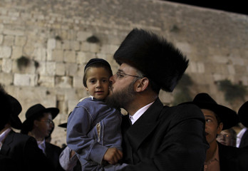 An Orthodox Jewish worshipper kisses a child while singing and praying at the Western Wall, Judaism's holiest prayer site, in Jerusalem's Old City