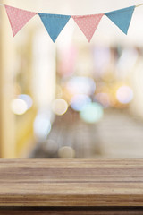 Empty wood table over colorful party flags and blur bokeh background, new year, christmas, festival background, banner