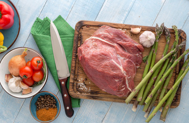 Raw meat beef on blue wooden table with different vegetables