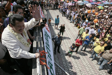 Former Philippine President Estrada waves at residents outside a church who are waiting in line to get their gift bags in Manila