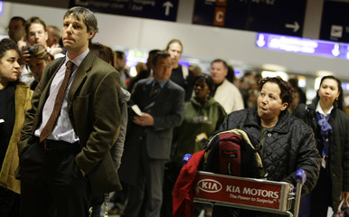 Passengers wait in a long queue outside a security check during a warning strike at Frankfurt airport