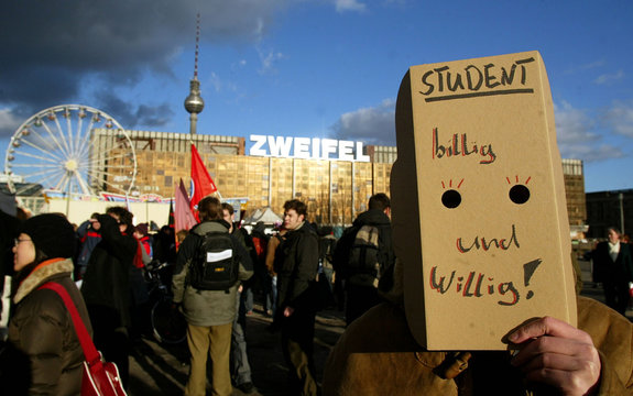 A student covers his face during a demonstration against plans to introduce fees for students at Ger..
