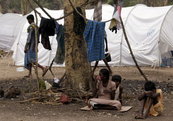 A Tamil woman sits with her children next to their tent at the Manik Farm refugee camp located on the outskirts of Vavuniya