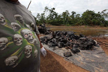 Ecuadorean oil worker wears a t-shirt with a skull design while working in an oil pit in Shushufindi