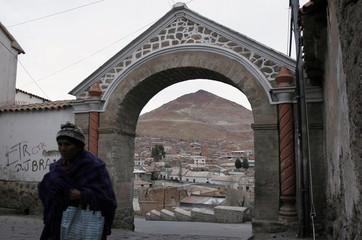 "A woman walks in Potosi with the ""Cerro Rico"" mountain in the background in Potosi"