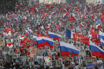People carry flags and pictures of World War Two soldiers as they take part in Immortal Regiment march during tVictory Day celebrations, marking 72nd anniversary of victory over Nazi Germany in World War Two, in central Moscow