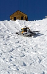A snowcat starts to plow fresh snow at the start of the men's Olympic downhill run at the Snowbasin ..