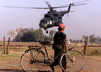 AFGHAN BOY WATCHES A NORTHERN ALLIANCE HELICOPTER.