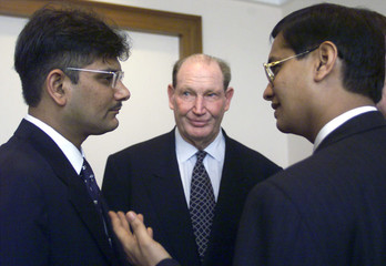 Australia's tycoon Kerry Packer (C) watches business partners Ketan Parekh (L) and Vinay Maloo (R) d..