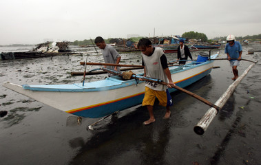 Filipino fishermen move their boat to a safer place at the Manila bay