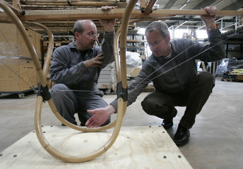 Ellingsen listens to Mayerhofer at the rear end of an unfinished 1914 Bleriot XI-2 replica in Vienna
