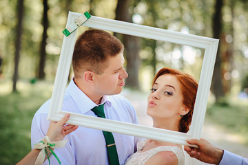 groom and bride posing in a white frame