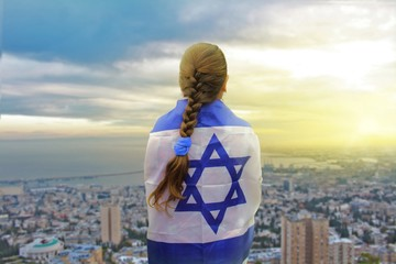 Lonely patriot jewish girl standing and looking at the sunrise in Haifa with the flag of Israel wrapped around her. Newcomer life and immigration to Israel concept.