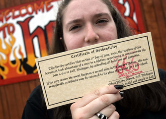 Visitor holds up her Certificate of Authenticity received while visiting Hell, Michigan