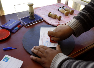 The postmaster stamps a customer's postcards from post office located near base camp of Mount Everest