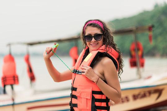 A girl on the beach in a life jacket and glasses looking at the camera and smile