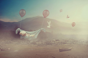 Adorable baby flying with balloons in a valley