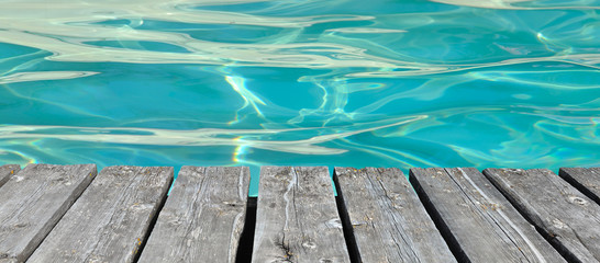 wooden floor on blue water of a swimming pool