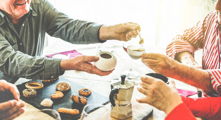 Group of senior people toasting italian style moka coffee after lunch
