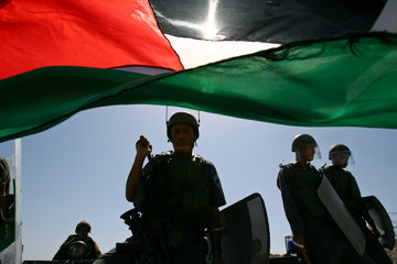 Israeli border police face Palestinian demonstrators during a protest in Bilin