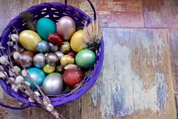 On the old wooden shabby table a dish with painted in different colors Easter eggs with feathers willow