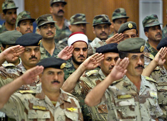 IRAQI AND JORDANIAN OFFICERS SALUTE DURING GRADUATION CEREMONY.