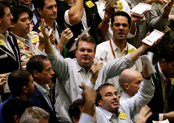 Traders shout across the crude oil pit during trading activity at the New York Mercantile