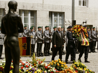 State Prime Minister of Schleswig-Holstein Carstensen walks behind soldiers of the German armed forces carrying a wreath of flowers in Berlin