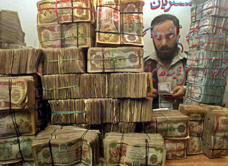 An Afghan money changer counts money at his shop in Kabul October 26, 2002. Afghanistan's security o..