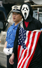 JAPANESE PROTESTER WALKS PAST A POLICE OFFICER AT AN ANTI-WAR AND ANTI-WEF RALLY IN SEOUL.
