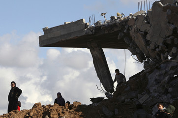 Palestinian woman stands in front of her destroyed house in Jabalya