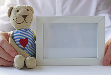 White photo frame in hands.
