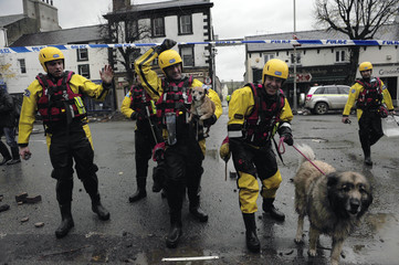 Rescue workers are seen with rescued dogs in Cockermouth