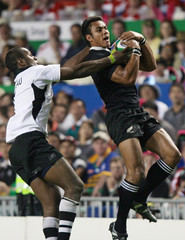 New Zealand's Wulf and Fiji's Delasau leap for the ball during Rugby World Cup Sevens final in Hong Kong.
