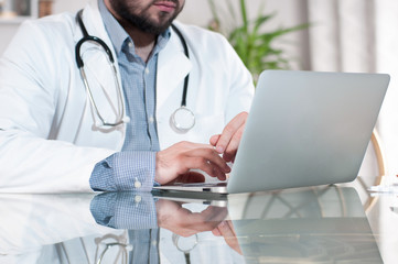 Doctor working on desk with laptop computer