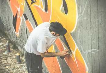Graffiti artist covering his face while painting with aerosol color spray on the wall