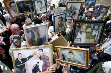 Palestinians hold pictures of jailed relatives during a protest in Tulkarm