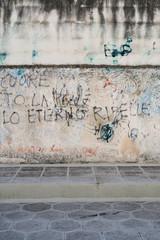 Graffiti about rebellion on italian wall.