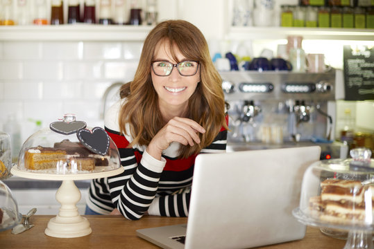 Welcome my cafe. Shot of a happy coffee owner woman working on laptop at the counter. Small business.