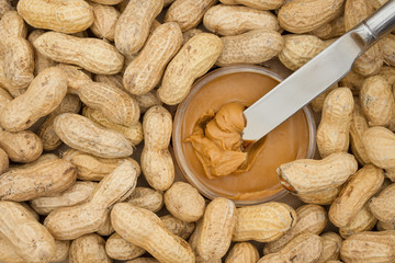 Peanut butter and raw peanuts in shells