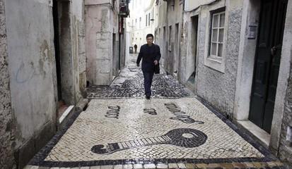 A man walks next to tiles depicting a Portuguese guitar of Fado in the Mouraria neighbourhood in Lisbon