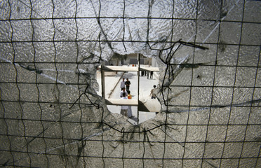 Students are seen through a shattered glass window of a school after a mortar attack in Baghdad