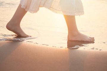 Girl Barefoot are Walking on the Beach in Water. Vacation in Summer at the Sea