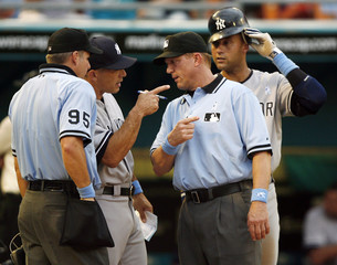 New York Yankees manager Joe Girardi argues with umpires as the Yankees' Derek Jeter looks on during eighth inning against the Florida Marlins in Miami
