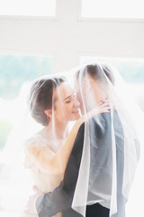 .Beautiful bride and groom portrait with veil over face. Stylish Loving wedding couple kissing and hugging