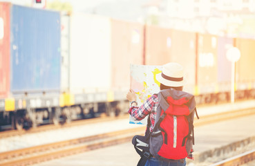 Traveler women wearing backpack holding map, waiting for a train...