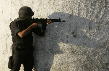 A member of an elite Brazilian police force takes cover during a raid in Rio de Janeiro