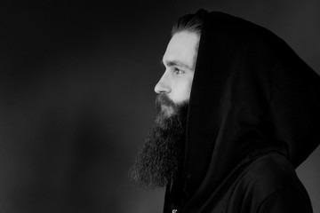 Portrait of handsome stylish serious man in a hood. Brutal man with a beard over black background