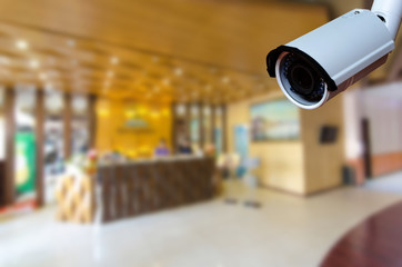 cctv security camera with abstract blurred hotel lobby interior for background, security technology concept.